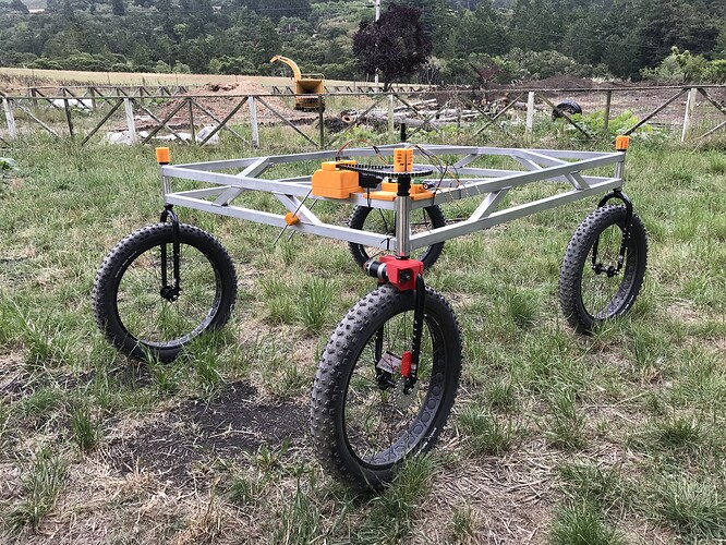 A photo showing our robot under development. It is a bare aluminum frame with some mountain bike parts, but no solar panels and only two of the normally eight motors.